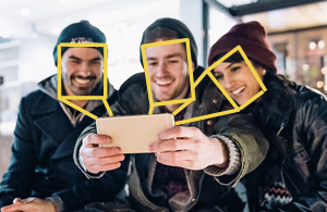 Three people taking a selfie with graphic boxes outlining their faces